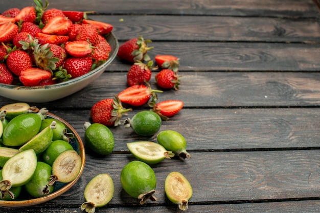 Widok z przodu czerwone truskawki ze świeżymi feijoas na ciemnym drewnianym rustykalnym biurku letni kolor soku z jagód jagodowych