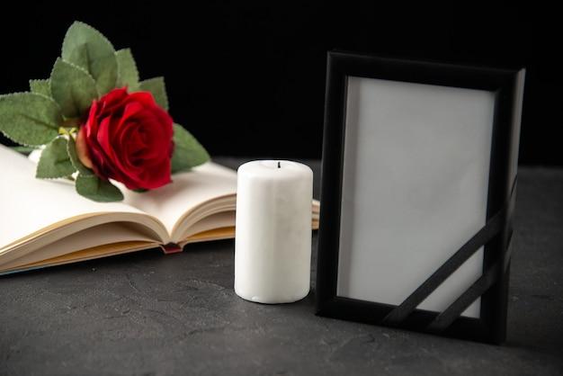 Widok z przodu czerwonej róży z książką i ramką na zdjęcia na czarno