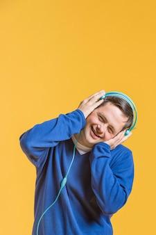Widok z przodu człowieka buźkę słuchania muzyki na słuchawkach