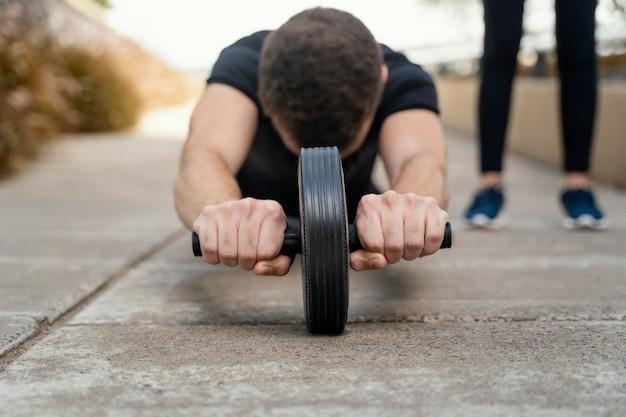 Widok z przodu człowieka ćwiczeń z kołem ab na zewnątrz