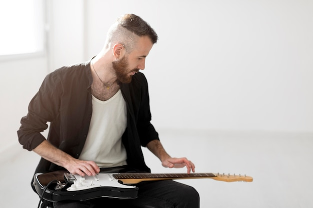Widok z przodu człowieka grającego na gitarze elektrycznej