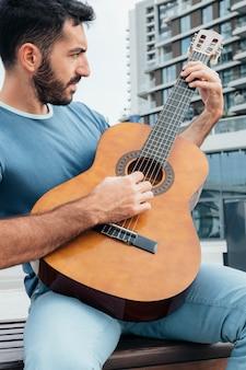 Widok z przodu człowieka grającego na gitarze