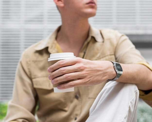 Widok z przodu człowieka na zewnątrz trzymając filiżankę kawy