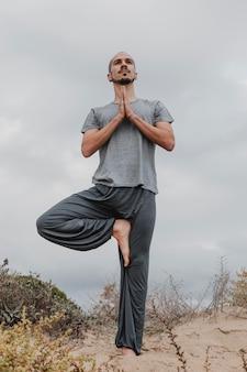 Widok z przodu człowieka na zewnątrz w pozycji jogi