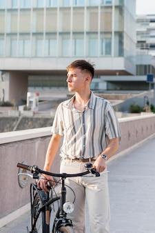 Widok z przodu człowieka na zewnątrz z rowerem
