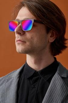 Widok z przodu człowieka, noszącego szare ubrania i okulary przeciwsłoneczne z wielobarwnymi soczewkami
