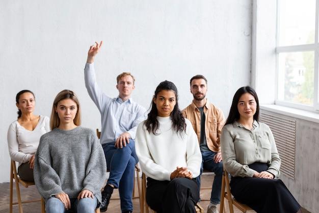 Widok z przodu człowieka podnoszącego rękę do zadawania pytań podczas sesji terapii grupowej