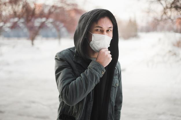 Widok z przodu człowieka pozowanie podczas noszenia maski medyczne