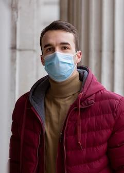 Widok z przodu człowieka pozującego na zewnątrz z maską medyczną