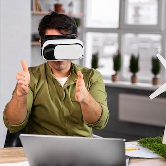 Widok z przodu człowieka pracującego nad ekologicznym projektem energii wiatrowej z zestawem słuchawkowym wirtualnej rzeczywistości
