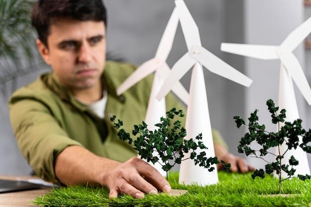 Widok z przodu człowieka pracującego nad projektem ekologicznej energii wiatrowej z turbinami wiatrowymi
