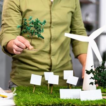 Widok z przodu człowieka pracującego nad układem projektu ekologicznej energii wiatrowej z turbinami wiatrowymi