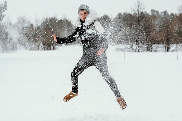 Widok z przodu człowieka skaczącego na zewnątrz w zimie