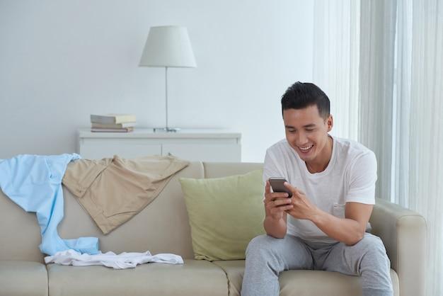 Widok z przodu człowieka sms-y do przyjaciół w domu i uśmiechnięty
