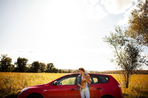Widok z przodu człowieka trzymającego kota przed samochodem