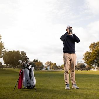 Widok z przodu człowieka z lornetką na polu golfowym