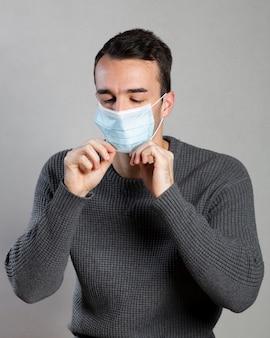 Widok z przodu człowieka zakładającego maskę medyczną w celu zapobiegania