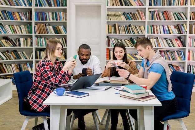Widok z przodu czterech przyjemnych, uśmiechniętych wieloetnicznych uczniów w wieku 25 lat, korzystających ze smartfonów w sieciach społecznościowych podczas przerwy w nauce