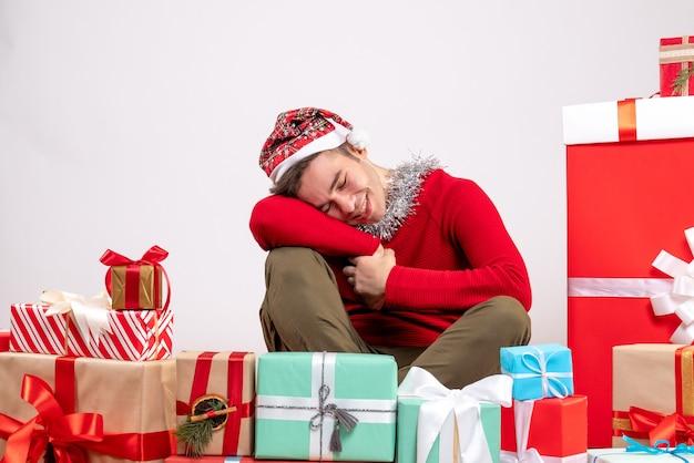 Widok z przodu daydreamer młody człowiek z maską siedzi wokół świątecznych prezentów
