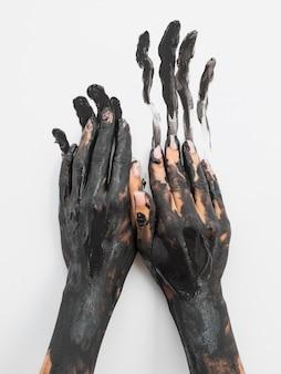 Widok z przodu dłoni pomalowanych czarną farbą