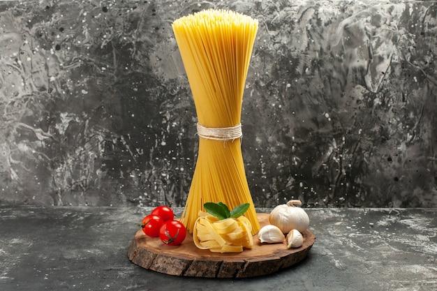Widok z przodu długi włoski makaron z czerwonymi pomidorami i czosnkiem na jasnoszarym cieście w kolorze żywności kuchnia zdjęcie posiłek