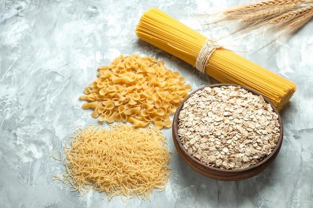 Widok z przodu długi włoski makaron z różnymi kształtami surowego małego makaronu na jasnym zdjęciu kolor żywności wiele ciasta