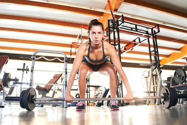 Widok z przodu dopasowanej młodej kobiety podnoszącej sztangę patrząc skoncentrowany, ćwicząc w samej siłowni.