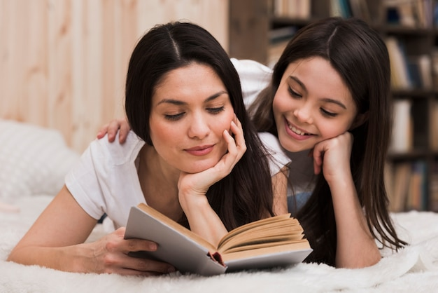 Widok z przodu dorosła kobieta i dziewczyna czyta książkę