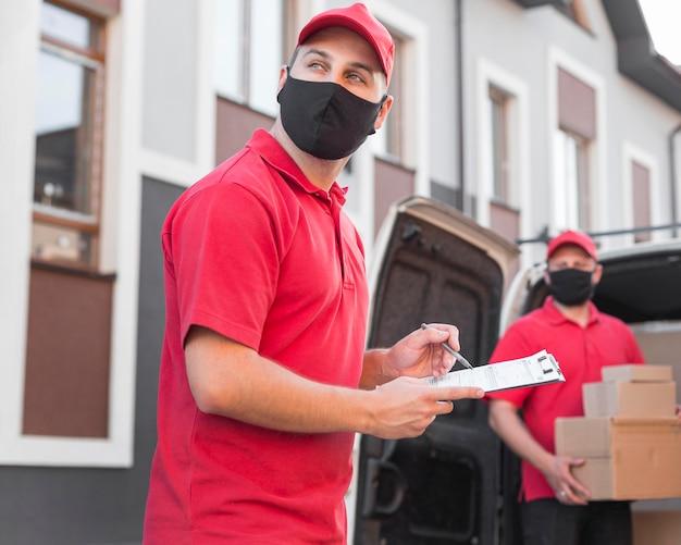 Widok z przodu dostawy mężczyzn z maską