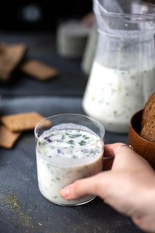 Widok z przodu dovga posypany pieprzem świeżym jak napój z zieleniną na szarym płynnym zupie