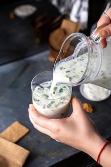 Widok z przodu dovga wlewa się do szklanki solonej świeżej papryki jak napój z zielenią na szarym tle płyn do zupy
