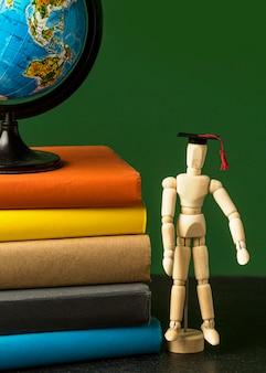 Widok z przodu drewnianej figurki z akademicką czapką i kulą ziemską
