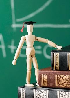 Widok z przodu drewnianej figurki z akademicką czapką i stosem książek