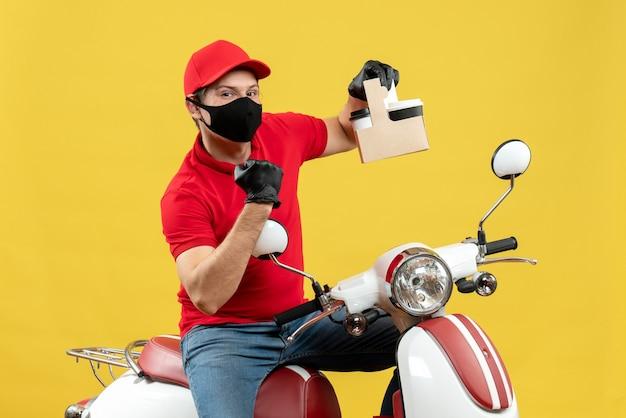 Widok z przodu dumnego kuriera w czerwonej bluzce i rękawiczkach w masce medycznej siedzi na skuterze pokazującym zamówienia