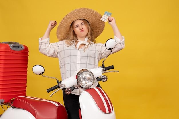 Widok z przodu dumnej młodej kobiety w kapeluszu, zbierając swój bagaż, siedząc na motocyklu i pokazując bilet