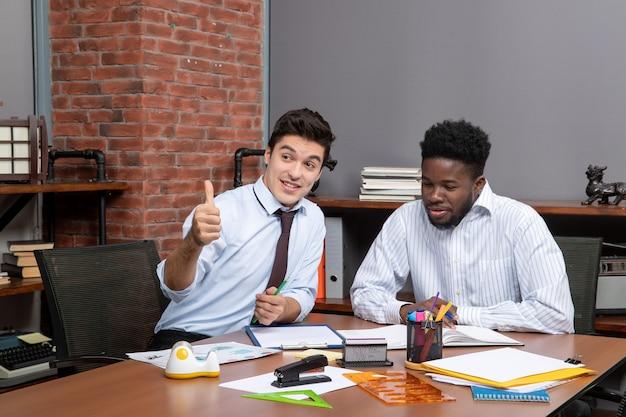 Widok z przodu dwóch biznesmenów omawiających projekt, podczas gdy jeden z nich daje kciuk w górę