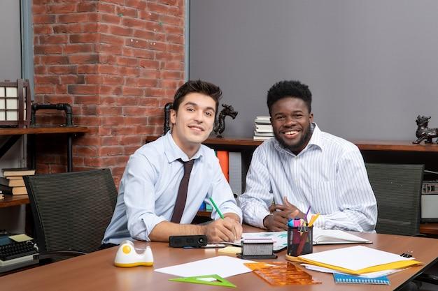 Widok z przodu dwóch biznesmenów patrzących na kamerę w biurze
