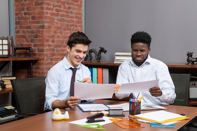 Widok z przodu dwóch biznesmenów posiadających dokumenty