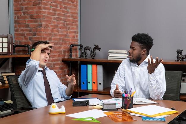 Widok z przodu dwóch biznesmenów w strojach wizytowych, siedzących przy stole z biurowymi rzeczami