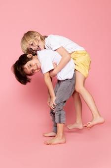 Widok z przodu dwóch chłopców bawiących się w białej koszulce na różowym biurku
