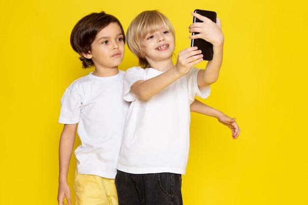 Widok z przodu dwóch chłopców w białych koszulkach biorących selfie na żółtym biurku