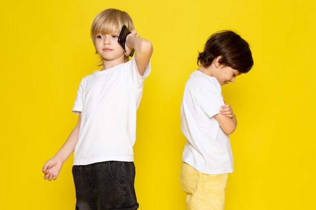 Widok z przodu dwóch chłopców w białych koszulkach na żółtym biurku