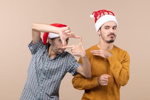 Widok z przodu dwóch ciekawskich facetów z czapkami mikołaja jeden robiący znak aparatu rękami na na białym tle