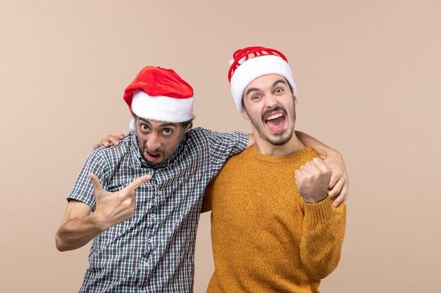 Widok z przodu dwóch entuzjastycznych facetów w czapkach mikołaja przytulających się na beżowym tle na białym tle