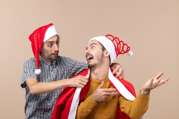 Widok z przodu dwóch facetów, jeden kładący płaszcz mikołaja na ramieniu przyjaciela na beżowym tle
