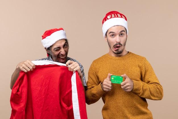 Widok z przodu dwóch facetów, jeden trzyma płaszcz mikołaja, a drugi z kartą kredytową patrząc na kamerę na beżowym tle na białym tle