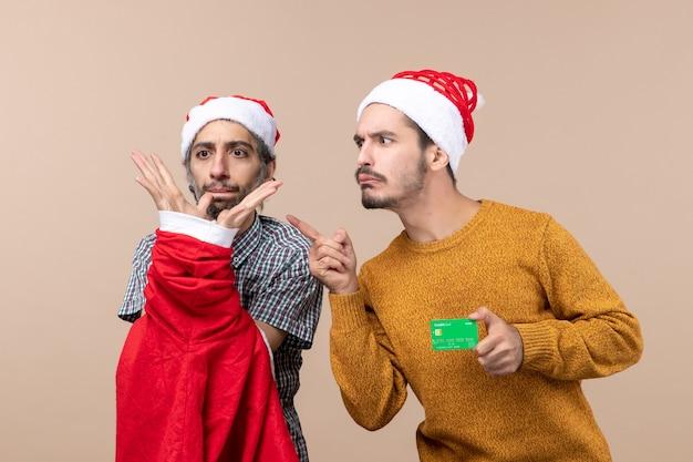 Widok z przodu dwóch facetów, jeden trzyma płaszcz świętego mikołaja, a drugi z kartą kredytową, patrząc na coś na beżowym tle na białym tle