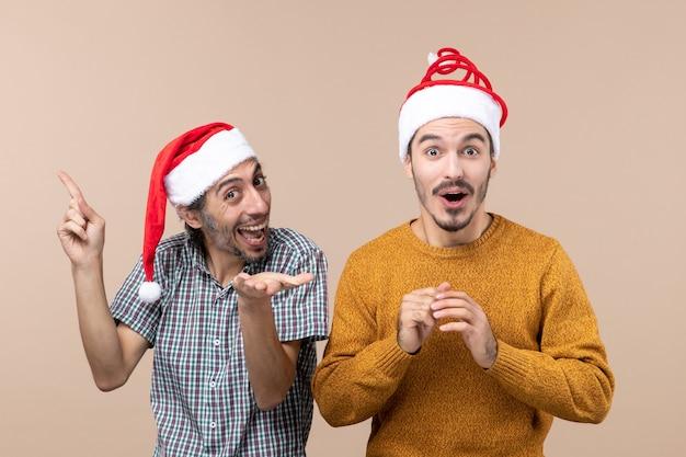 Widok z przodu dwóch facetów w czapkach mikołaja, jeden pokazujący coś, co drugi zaskakuje na beżowym tle