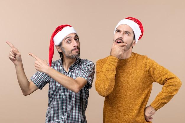 Widok z przodu dwóch facetów w czapkach mikołaja, jeden pokazujący coś, drugi myślący i przykładający dłoń do ust na beżowym, odizolowanym tle