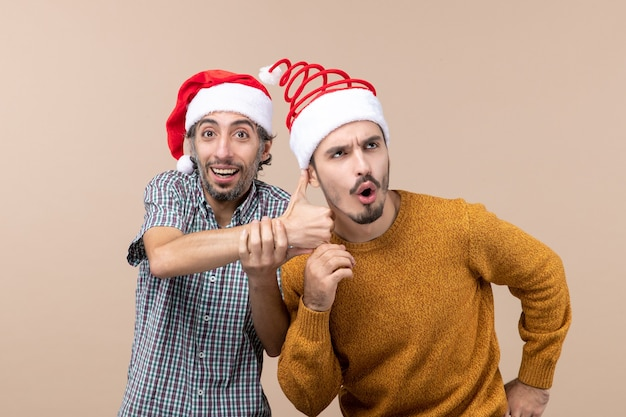 Widok z przodu dwóch facetów w czapkach mikołaja, jeden uśmiecha się i pokazuje drugiemu kciuk w górę na beżowym tle